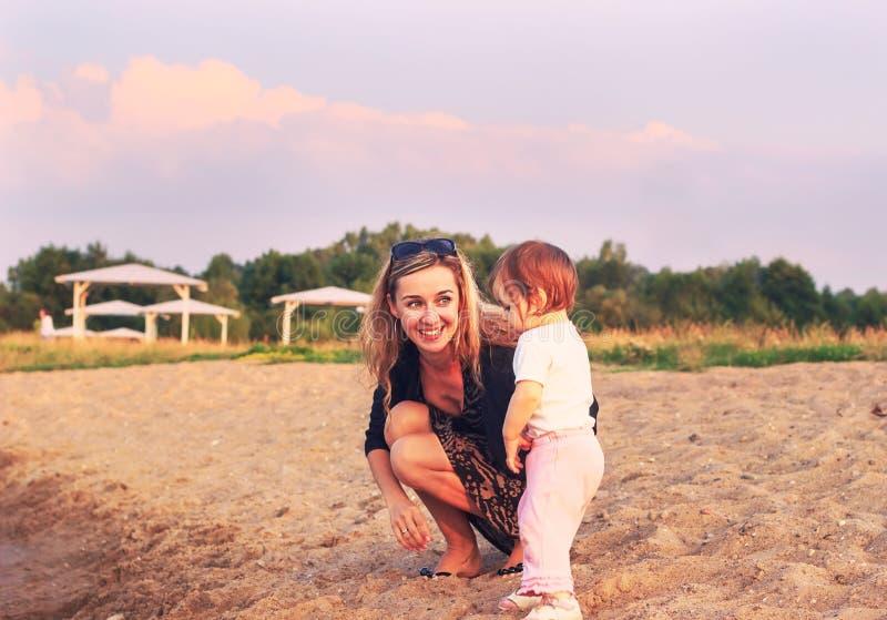 Madre e bambino che giocano sulla spiaggia al tempo di tramonto Concep immagine stock libera da diritti