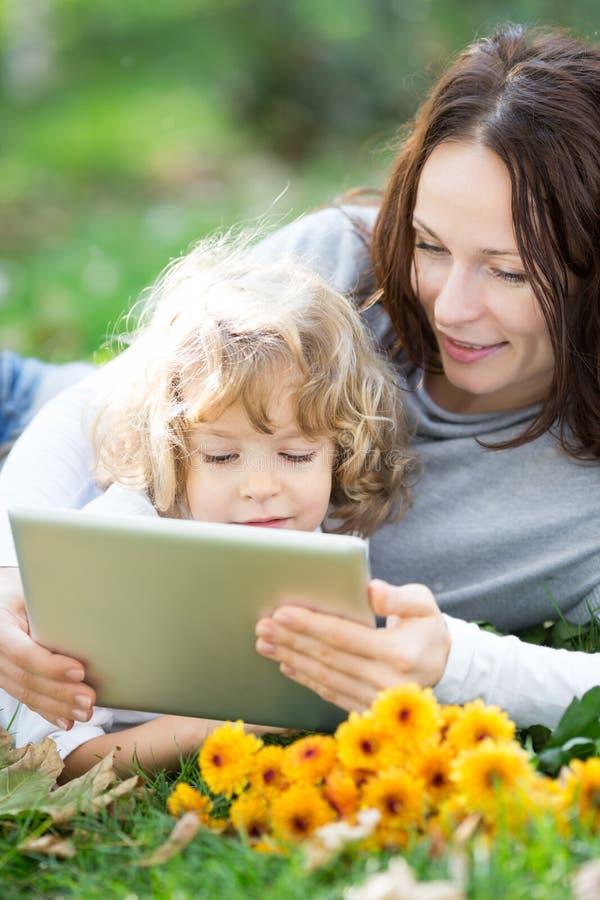 Madre e bambino che per mezzo del PC della compressa all'aperto fotografia stock libera da diritti