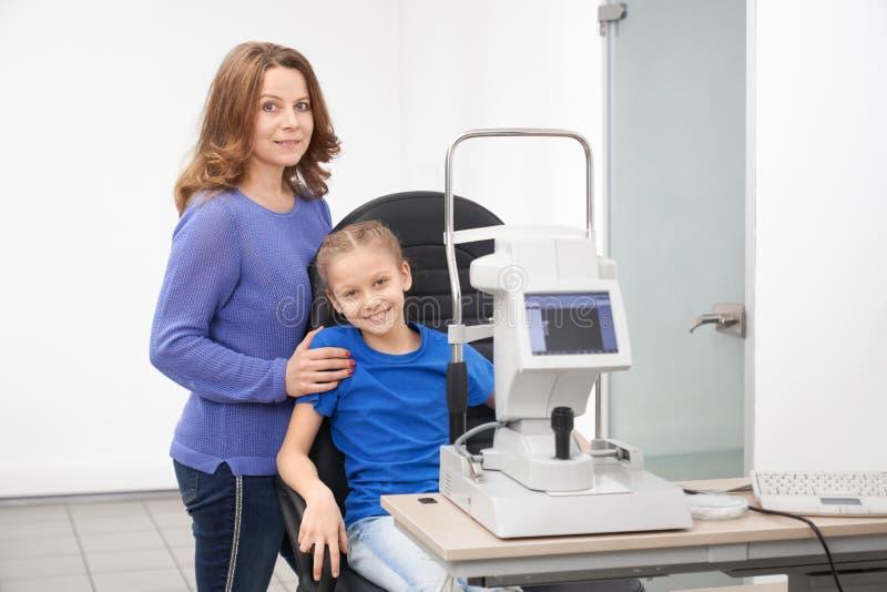 Madre e bambino che posano nella clinica moderna di oftalmologia immagine stock