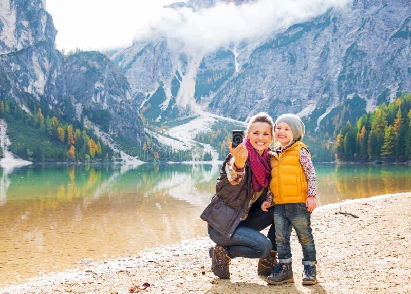 Madre e bambino che prendono la foto di auto sui braies del lago fotografia stock