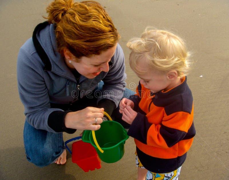 Madre e bambino che raccolgono le conchiglie fotografia stock libera da diritti