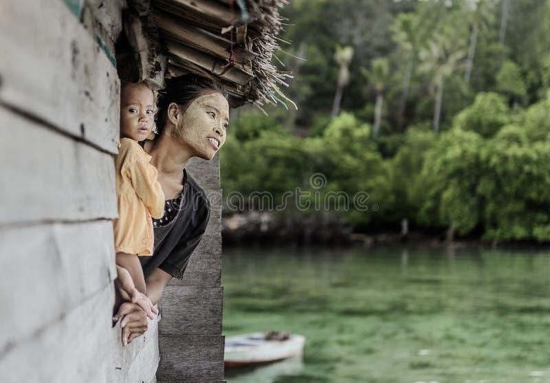 Madre e bambino che sembrano finestra esterna nel villaggio del mare di Semporna, Sabah Semporna, Malesia immagine stock