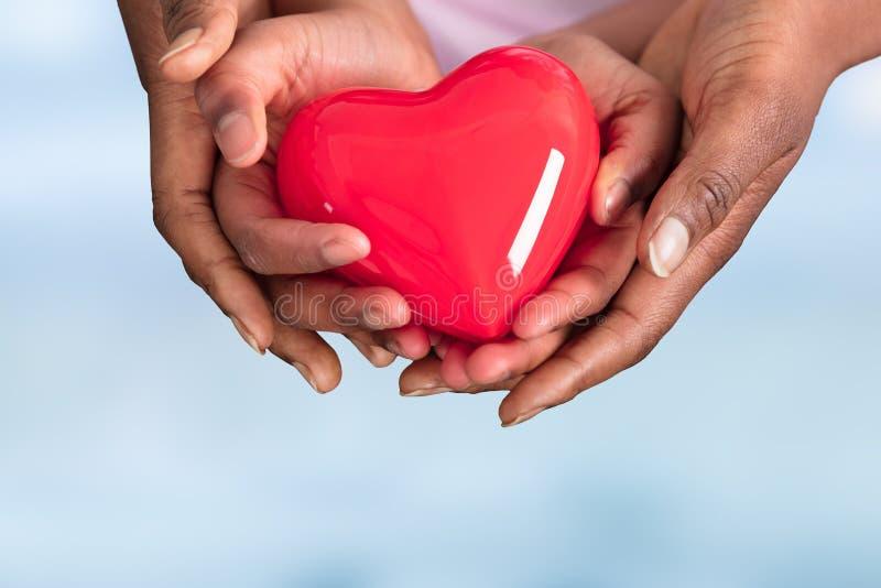 Madre e bambino che tengono cuore rosso fotografia stock libera da diritti