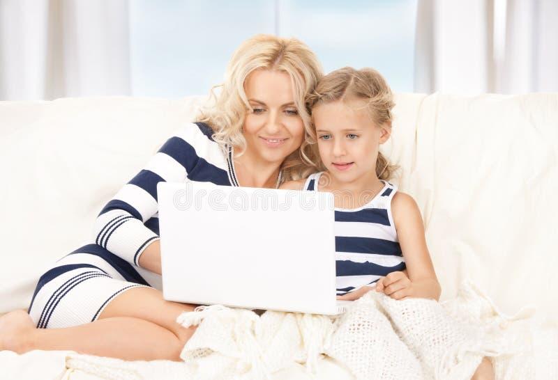 Madre e bambino felici con il computer portatile immagini stock libere da diritti