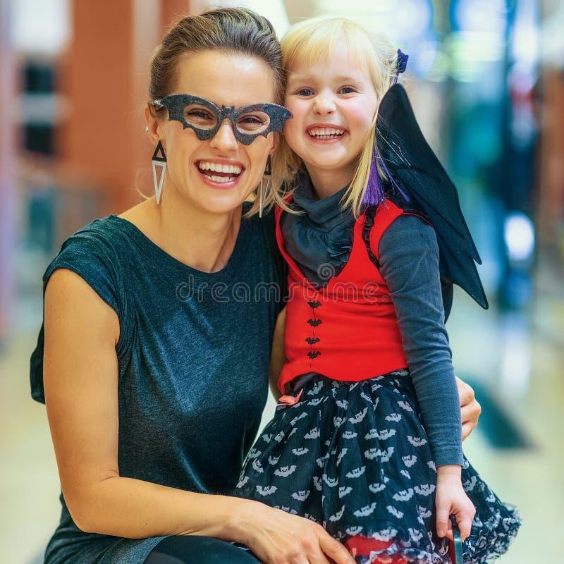Madre e bambino moderni felici su Halloween al centro commerciale fotografia stock