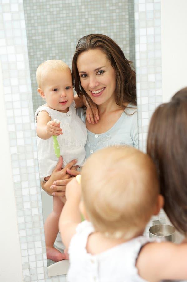 Madre e bambino nella riflessione dello specchio in bagno immagini stock libere da diritti