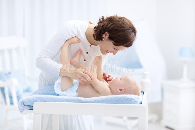 Madre e bambino in pannolino sulla tavola cambiante fotografia stock libera da diritti