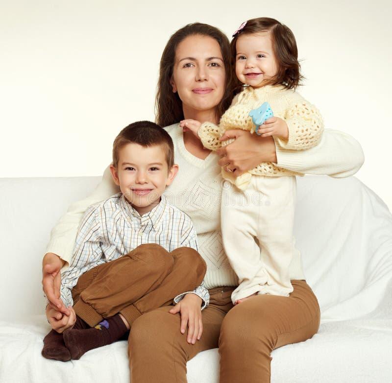 Madre e bambino, ritratto della famiglia su fondo bianco giallo tonificato immagine stock