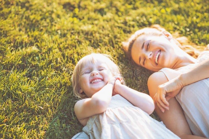 Madre e bambino sorridenti che mettono su prato immagine stock libera da diritti