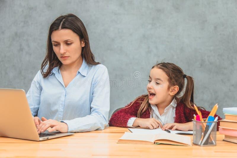 Madre e bambino su un fondo grigio Durante questa donna, lavorare per un computer portatile esamina il computer portatile Ragazza immagini stock libere da diritti