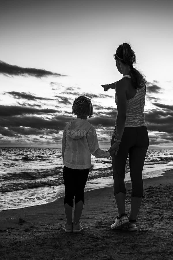 Madre e bambino sulla spiaggia sul tramonto che indicano a qualcosa immagine stock