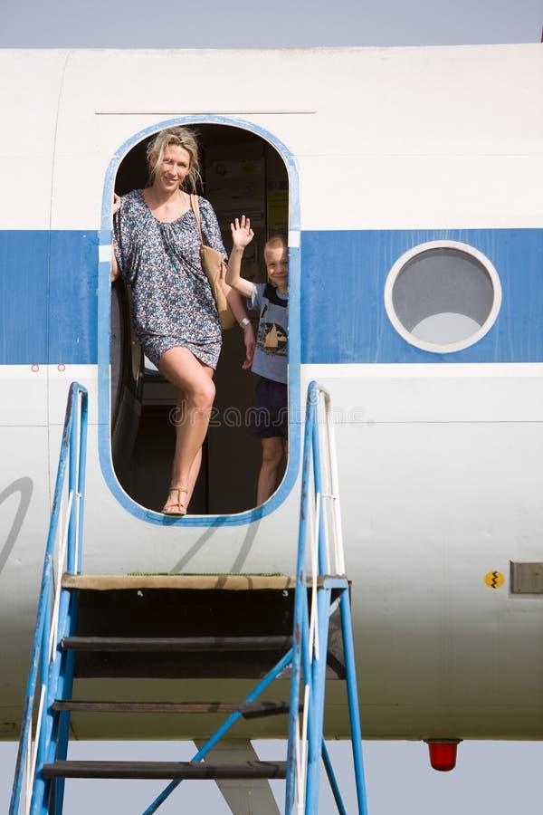 Madre e bambino, in una porta aperta di un aereo di parcheggio immagini stock libere da diritti