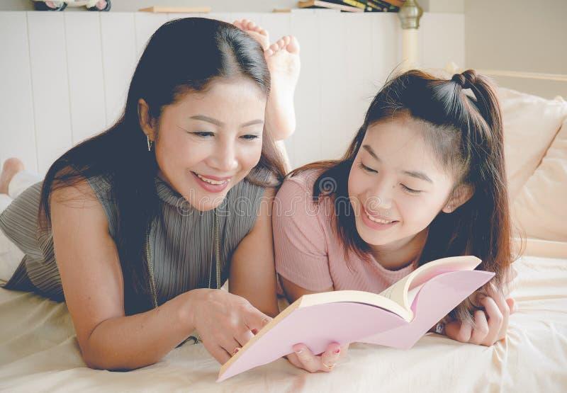Madre e derivato che leggono insieme un libro e felice a casa, fa immagini stock libere da diritti