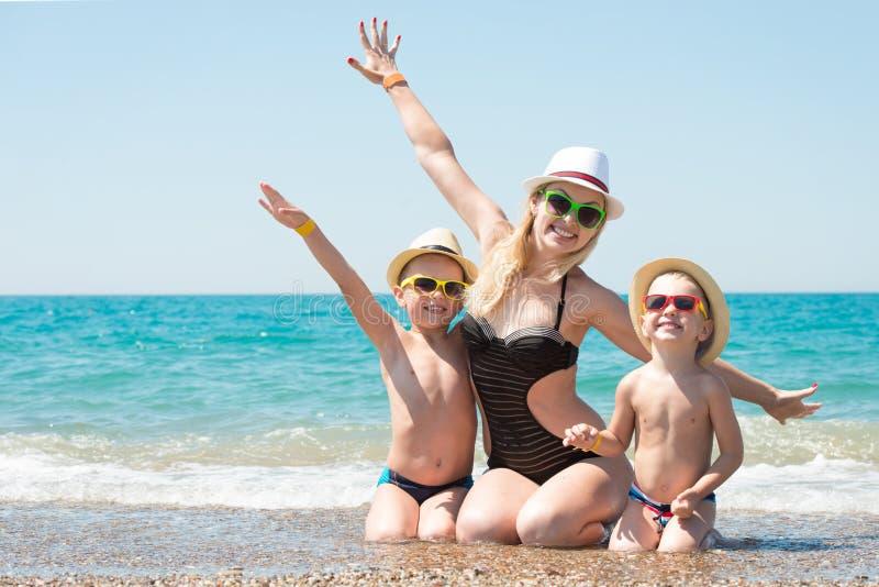 Madre e due figli in cappelli che si siedono sulla spiaggia Vacanza di famiglia di estate fotografie stock libere da diritti
