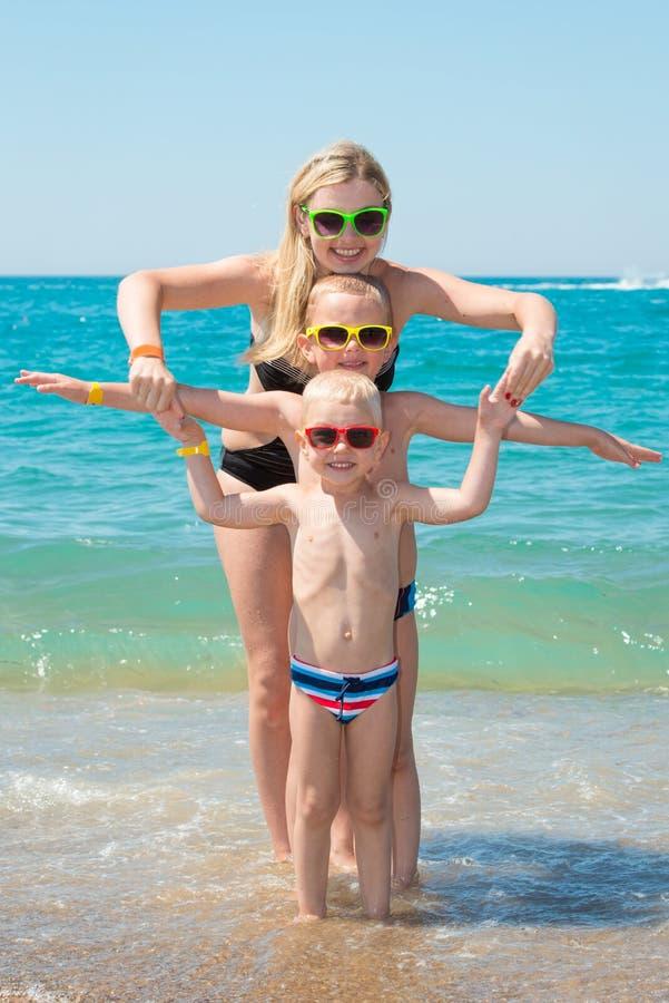 Madre e due figli in occhiali da sole che riposano e che giocano sulla spiaggia Vacanza di famiglia di estate immagini stock