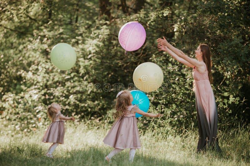 Madre e due figlie che si tengono per mano circonduzione tempo della famiglia insieme Tempo divertente Ragazze con i palloni Fuoc fotografia stock