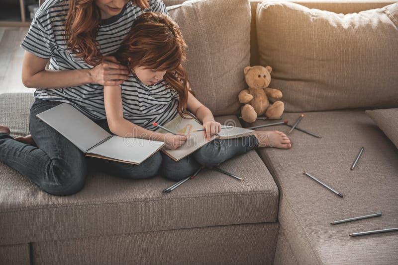 Madre e figlia assorbenti nel disegno a casa fotografia stock