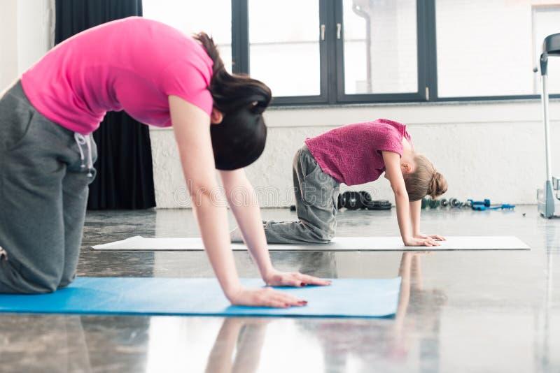 Ufficio Disegno Yoga : Madre e figlia in camice rosa che praticano yoga nella posa del
