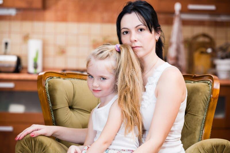 Madre e figlia che abbracciano all'interno immagine stock libera da diritti
