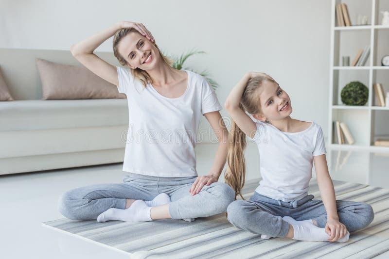 madre e figlia che allungano collo prima dell'esercitazione fotografia stock libera da diritti