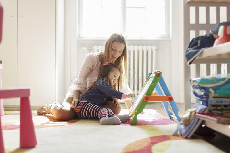 Madre e figlia che assorbono la stanza immagini stock libere da diritti