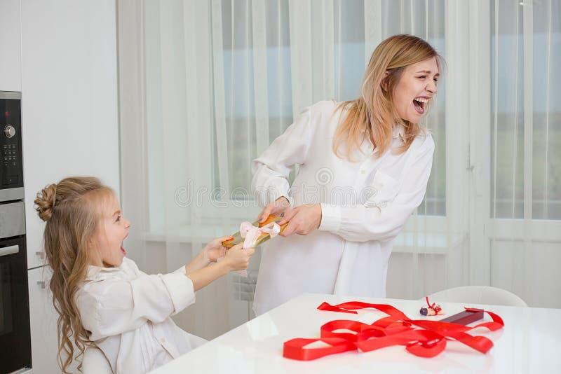 Madre e figlia a che avvolgono insieme un regalo fotografia stock