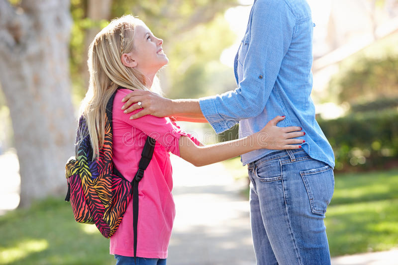 Madre e figlia che camminano alla scuola sulla via suburbana fotografia stock libera da diritti