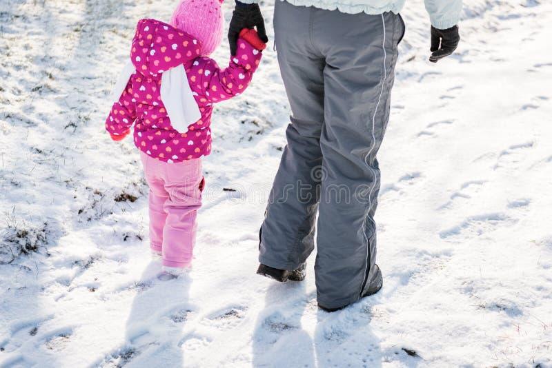 Madre e figlia che camminano insieme un giorno di inverno nevoso fotografia stock