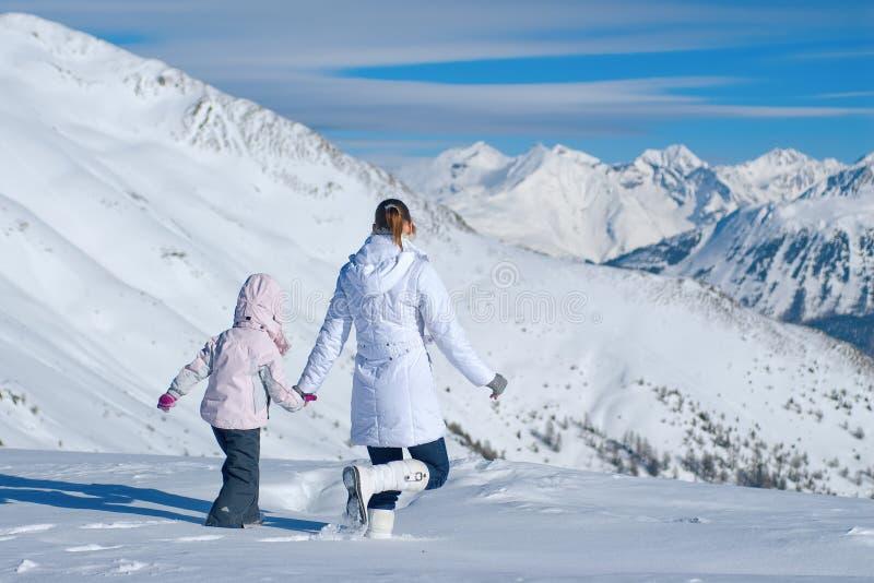 Madre e figlia che camminano nelle montagne di vasta neve fotografia stock
