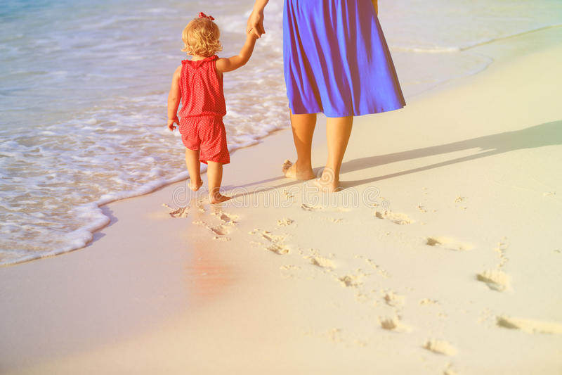 Madre e figlia che camminano sulla spiaggia che lascia orma in sabbia fotografia stock