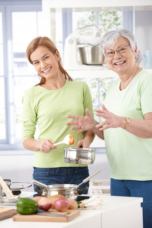 Madre e figlia che cucinano insieme sorridere fotografia stock libera da diritti