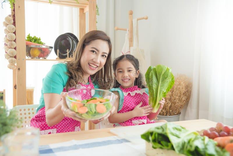 Madre e figlia che cucinano prima colazione in cucina immagini stock libere da diritti