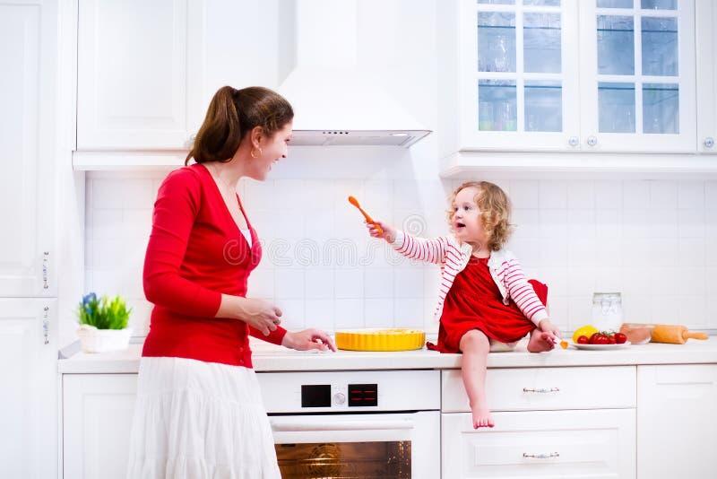 Madre e figlia che cuociono una torta immagine stock