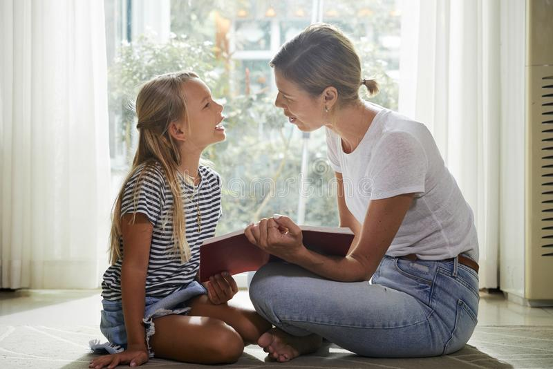 Madre e figlia che discutono libro immagini stock libere da diritti