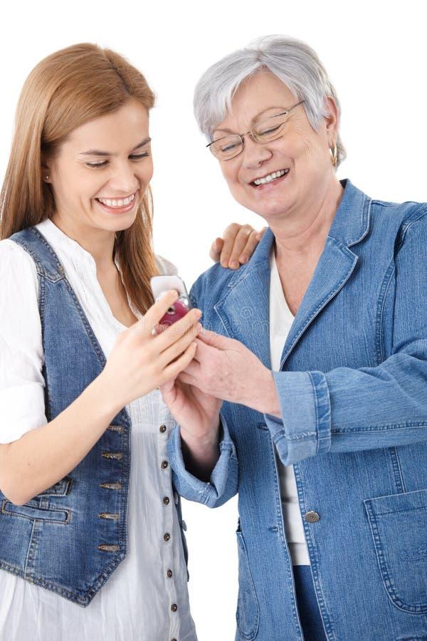 Madre e figlia che esaminano le foto sul mobile