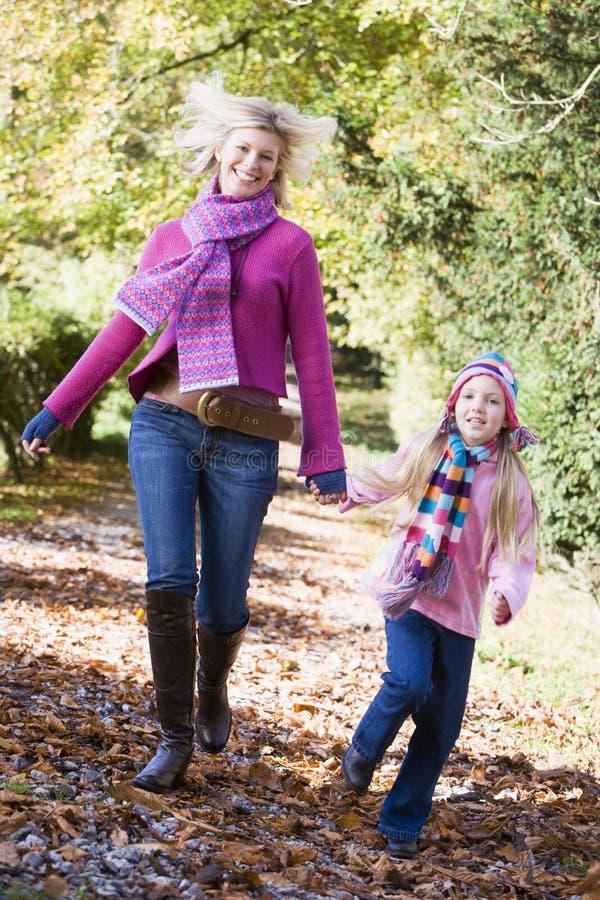 Madre e figlia che funzionano lungo il percorso fotografia stock