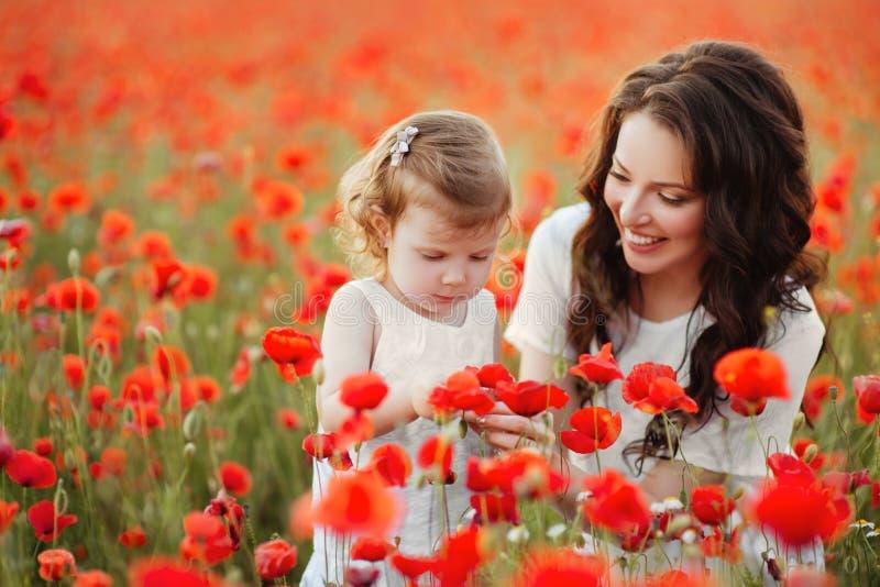 Madre e figlia che giocano nel giacimento di fiore immagini stock libere da diritti