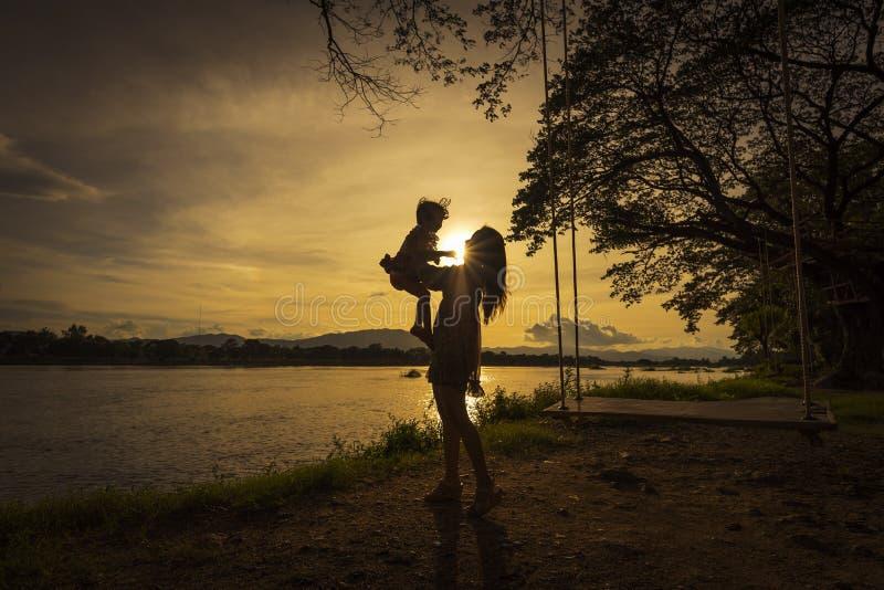 Madre e figlia che giocano sul lato del fiume fotografia stock