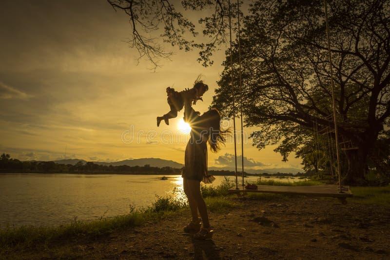 Madre e figlia che giocano sul lato del fiume immagine stock