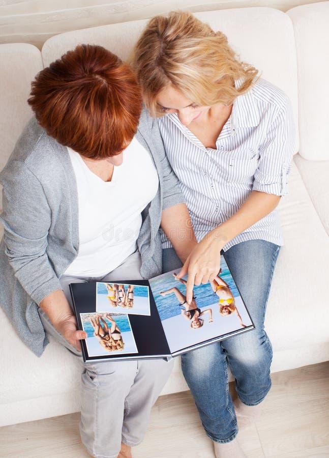 Madre e figlia che guardano il libro della foto fotografia stock