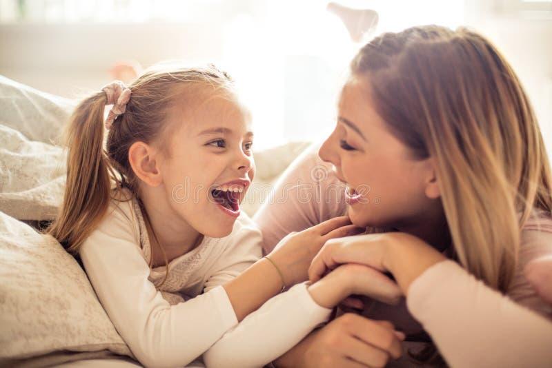 Madre e figlia che hanno conversazione a letto immagini stock libere da diritti