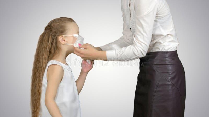 Madre e figlia che indossano le maschere chirurgiche per proteggere da un'epidemia su fondo bianco fotografie stock