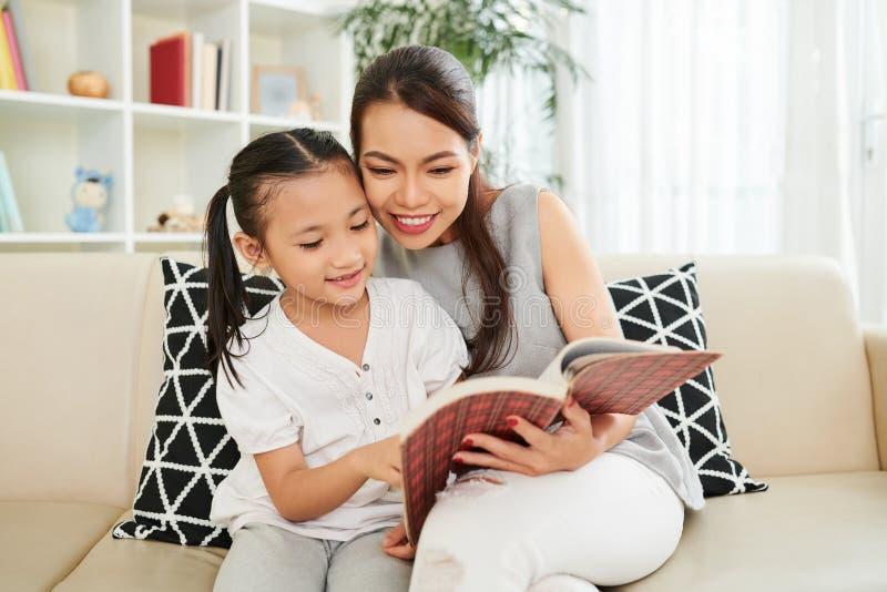 Madre e figlia che leggono un libro immagini stock