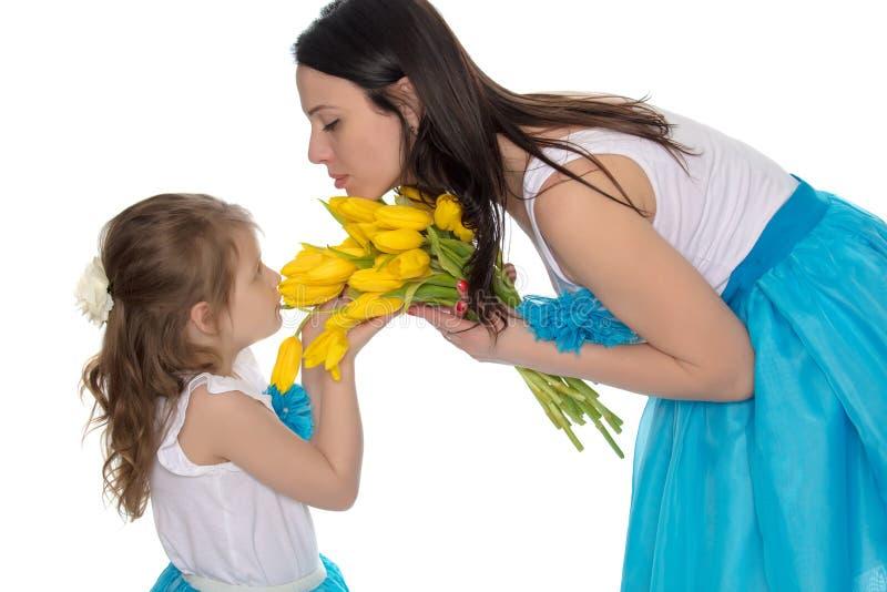 Madre e figlia che odorano i tulipani gialli fotografie stock