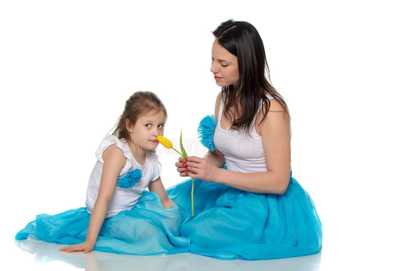 Madre e figlia che odorano i tulipani gialli immagini stock