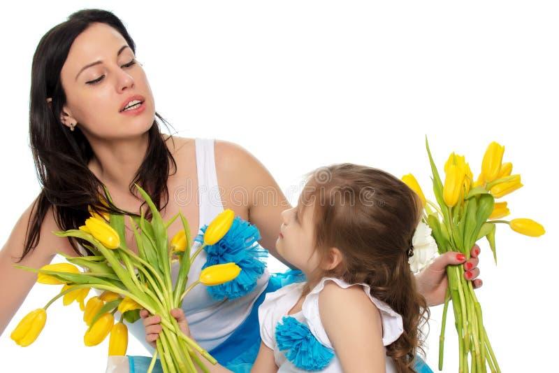 Madre e figlia che odorano i tulipani gialli fotografia stock libera da diritti