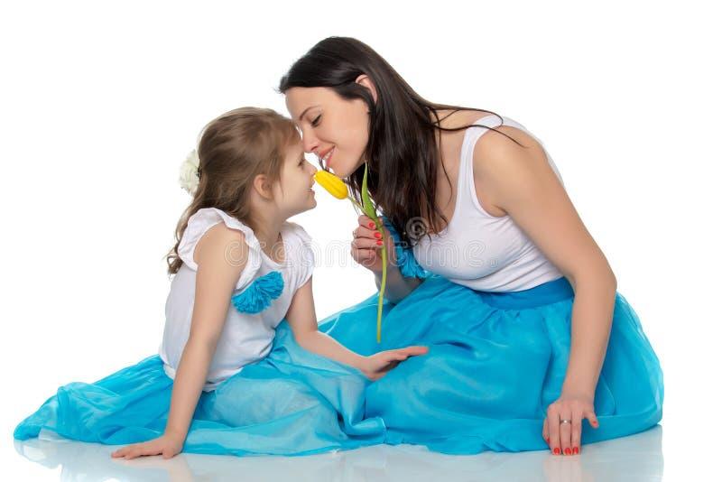 Madre e figlia che odorano i tulipani gialli fotografia stock