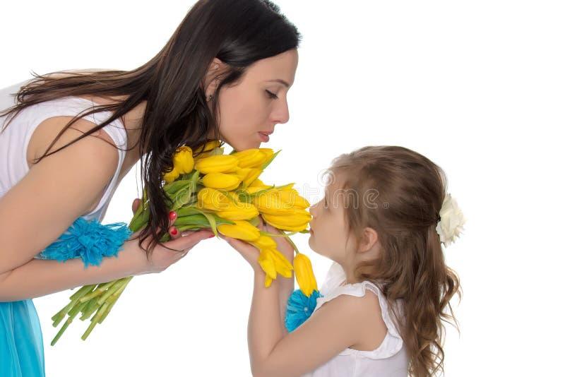 Madre e figlia che odorano i tulipani gialli immagine stock