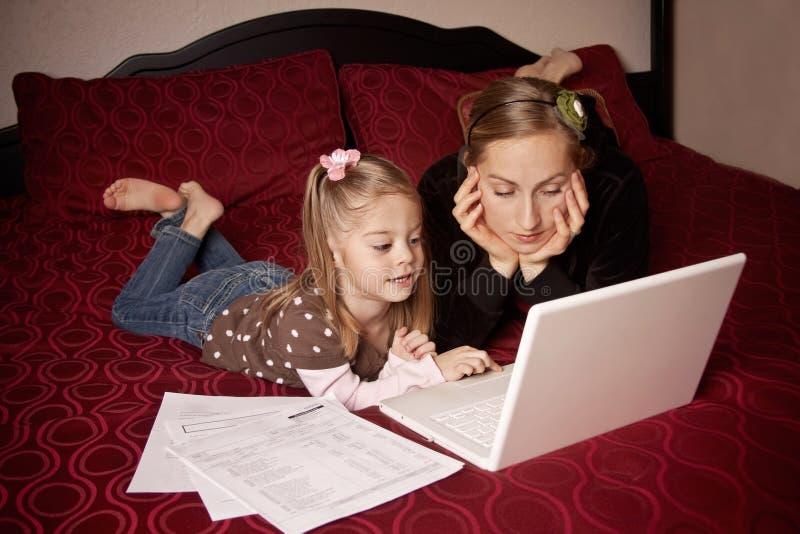 Madre e figlia che per mezzo del calcolatore immagini stock libere da diritti
