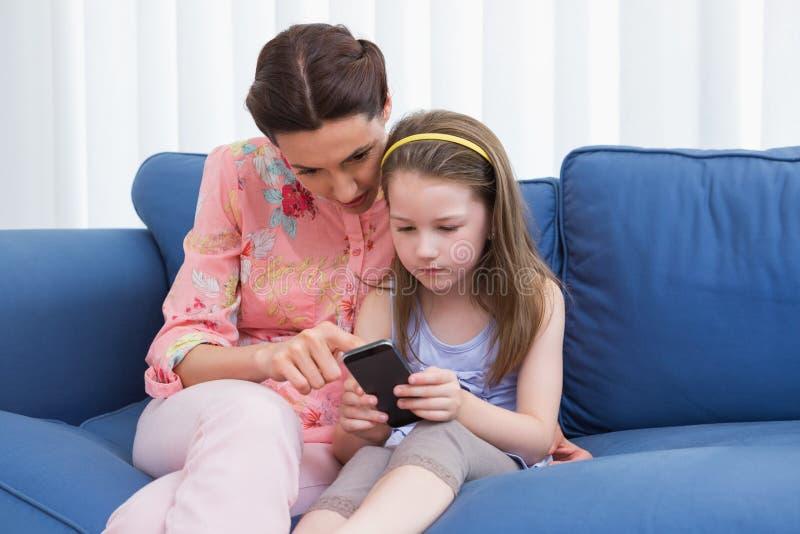 Madre e figlia che per mezzo dello smartphone sullo strato fotografia stock libera da diritti